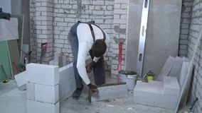 Jonge Kaukasische bouwer die mortier aan kanten van gelucht concreet blok zetten stock videobeelden