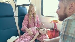 Jonge Kaukasische familie die samen - moeder, vader en weinig dochter die in de trein dichtbij het venster spreken reizen stock videobeelden