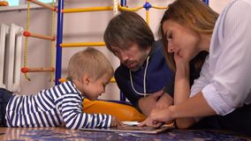 Jonge Kaukasische familie het letten op beelden in het boek samen Man, vrouw en leuk weinig jongen die vrije tijd hebben thuis stock videobeelden