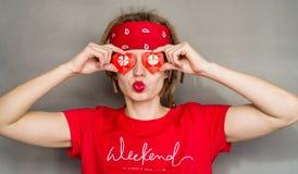 Jonge Kaukasische hipstervrouw met dreadlocks en rode hoofdband die haar ogen behandelen met origamiharten stock foto's