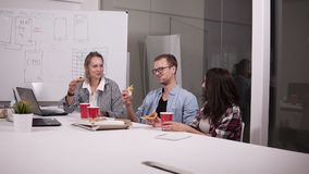 Jonge Kaukasische medewerkers die middagpauze hebben die pizza samen in bureau eten Lachend, sprekend, hebbend pret personeel stock video