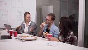 Jonge Kaukasische medewerkers die middagpauze hebben die pizza samen in bureau eten Lachend, sprekend, hebbend pret personeel stock videobeelden
