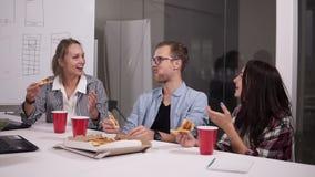 Jonge Kaukasische medewerkers die middagpauze hebben die pizza samen in bureau eten Lachend, sprekend, hebbend pret Voedsel stock footage