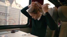 Jonge Kaukasische meisjesritten in een vervoer van de luxe interlokaal trein Maakt een kapsel uit haar Concept hoe te zijn stock footage