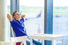 Jonge Kaukasische mens bij luchthaven binnenwachten voor royalty-vrije stock foto's