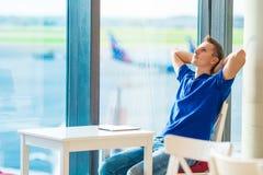 Jonge Kaukasische mens bij luchthaven binnenwachten voor stock afbeeldingen