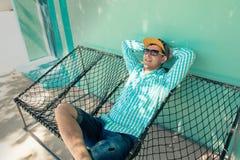 Jonge Kaukasische mens die in een hangmat prettige luiheid slingeren van weekendochtend Stock Afbeelding