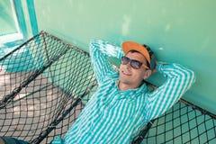 Jonge Kaukasische mens die in een hangmat prettige luiheid slingeren van weekendochtend Stock Afbeeldingen