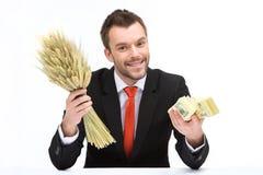 Jonge Kaukasische mens die verse tarwe en dollars houden Royalty-vrije Stock Foto
