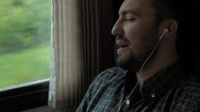 Jonge Kaukasische mens die zijn favoriet lied in een trein zingen stock videobeelden