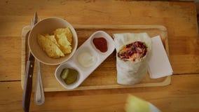 Jonge Kaukasische mens het onderdompelen nachos in saus terwijl het eten van Mexicaans voedsel Hoogste dichte omhooggaande mening stock video