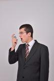 Jonge Kaukasische mens in kostuum die een astmainhaleertoestel met behulp van om PR te behandelen stock fotografie