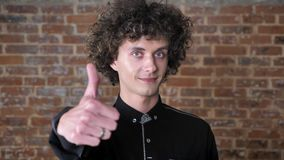 Jonge Kaukasische mens met krullend duimen tonen in camera en haar die, zeker mannetje, bakstenen muurachtergrond glimlachen stock videobeelden