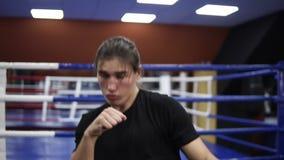 Jonge Kaukasische mens opleiding op boksring in moderne gymnastiek Het bestrijden van de schaduw Kickboxer in zwarte T-shirt en l stock video