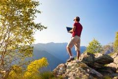 Jonge Kaukasische mensenzitting openlucht op een rots die aan een lapto werken Stock Afbeeldingen