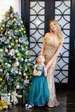 Jonge Kaukasische moeder en weinig dochter die kleding dragen die zich dichtbij Kerstboom bevinden royalty-vrije stock afbeelding