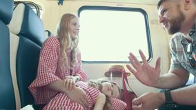 Jonge Kaukasische moeder, vader en weinig dochter die samen en in de trein dichtbij het venster spreken reizen stock videobeelden