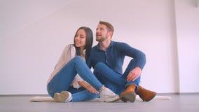 Jonge Kaukasische paarzitting op vloer van nieuwe en flat die zijnd gelukkig koesteren kussen stock footage