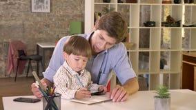 Jonge Kaukasische vader die zijn zoon houden en hem onderwijzen hoe te schrijven, zittend in modern bureau stock footage