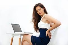 Jonge Kaukasische vrouw die chronische rugpijn/rugpijn/bureausyndroom hebben terwijl het werken met laptop aan wit bureau Royalty-vrije Stock Foto's