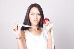 Jonge Kaukasische vrouw die een een maatregelenband en appel houden Stock Fotografie