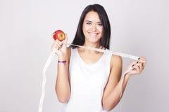 Jonge Kaukasische vrouw die een een maatregelenband en appel houden Stock Afbeeldingen