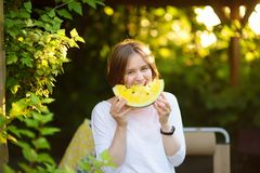 Jonge Kaukasische vrouw die gele watermeloen in openlucht eten stock afbeeldingen