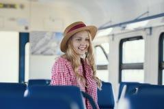 Jonge Kaukasische vrouw die in hoed met golvend haar in snelheidstrein glimlachen stock foto