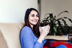 jonge Kaukasische vrouw die koffie of thee thuis voor ontbijt hebben thuis Sluit omhoog mening stock foto