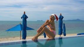 Jonge Kaukasische Vrouw in Santa Claus Hat Relaxing in Zwembad stock video