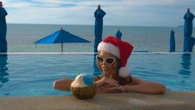 Jonge Kaukasische Vrouw in Santa Claus Hat Relaxing in Zwembad Kerstmis in Tropisch Land stock footage