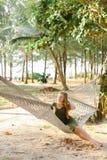 Jonge Kaukasische vrouwenzitting blootvoets op rieten hangmat, zand en bomen op achtergrond Stock Fotografie