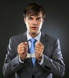 Jonge Kaukasische zakenman met de handboeien om:doen handen stock afbeelding