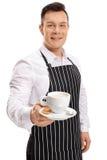 Jonge kelner die een kop van koffie aanbieden Stock Afbeelding