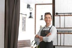 Jonge kelner in schort stock foto