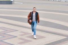 Jonge kerel alleen in leerjasje die onderaan de straat op steenweg lopen stock foto's