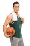 Jonge kerel die een basketbal houden Stock Afbeelding