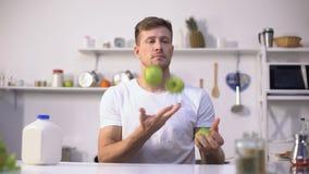 Jonge kerel die met groene appelen jongleren, die dieet en gezonde levensstijl, vitaminen beginnen stock videobeelden