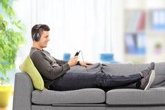 Jonge kerel die op bank liggen en aan muziek luisteren Royalty-vrije Stock Foto's