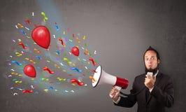 Jonge kerel die pret hebben, die in megafoon met ballons schreeuwen Royalty-vrije Stock Foto's
