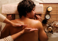 Jonge kerel in een schoonheidssalon die massage krijgt stock afbeeldingen