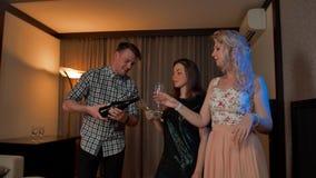 Jonge kerel gietende champagne in glazen van twee sexy dames stock video