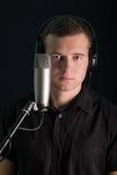 Jonge kerel met de studiomicrofoon Royalty-vrije Stock Afbeelding