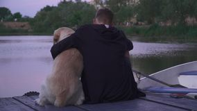 Jonge kerel met een hond op de pijler dichtbij het meer stock footage