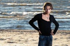 Jonge kerel op de achtergrond van het zonsondergangoverzees Royalty-vrije Stock Fotografie