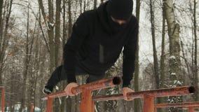 Jonge kerel in zwarte sportkleding met kap en Balaclava ninja die opdrukoefeningen met handen uitvoeren en voeten op de bars in stock videobeelden