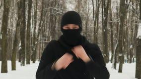 Jonge kerel in zwarte sportkleding met kap en Balaclava ninja die stempels in motie in de de winter snow-covered stad uitvoeren stock video