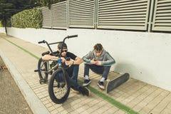 Jonge kerels die op mobiel op de straat letten Moderne levensstijl van jongeren stock foto's