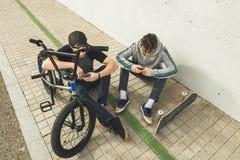 Jonge kerels die op mobiel op de straat letten Moderne levensstijl van jongeren royalty-vrije stock afbeeldingen
