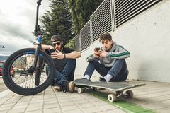 Jonge kerels die op mobiel op de straat letten Moderne levensstijl van jongeren royalty-vrije stock afbeelding